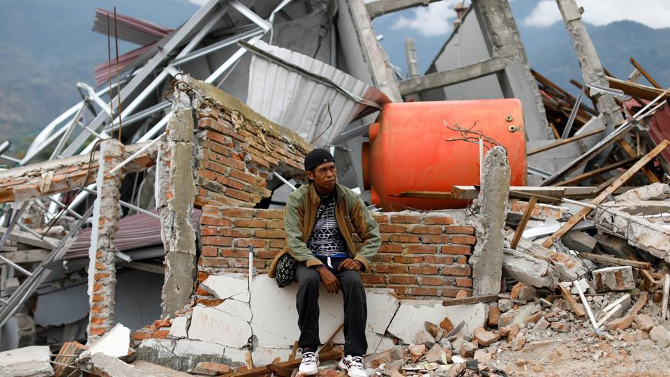 Nofal Surya, 37, sits on bricks that used to be his home hit by an earthquake, in Balaroa neighbourhood, Palu, Central Sulawesi, Indonesia, October 11, 2018. Surya said he lost around 15 members of his extended family and only seven have been found.