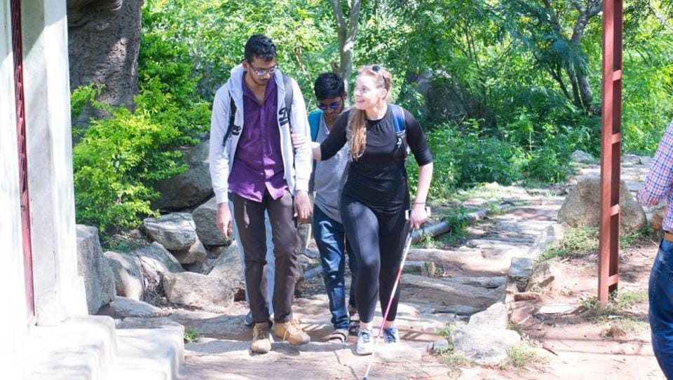 Cambria Sawyer from the Bikat Adventures team helps a blind individual during the trek.