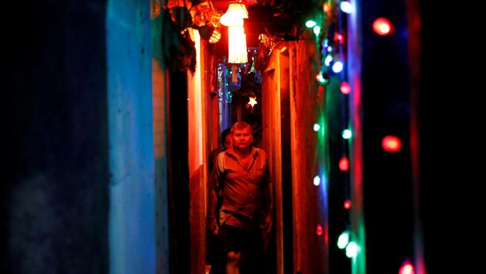 Residents walk in a slum's alley illuminated by colourful lights in Mumbai. (Danish Siddiqui  / REUTERS)