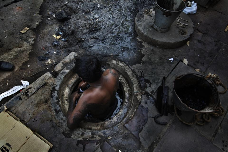 Municipal worker attempts to unblock a sewer overflowing with human excreta in New Delhi. Although a law bans manual scavenging - the manual removal of human excreta from 'dry toilets' - the practice is widespread across cities and towns in India.