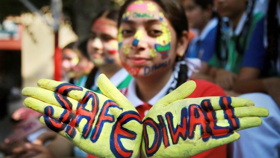 A student displays a message painted on her hands to create awareness regarding the hazardous effects of air pollution during Diwali in Jammu