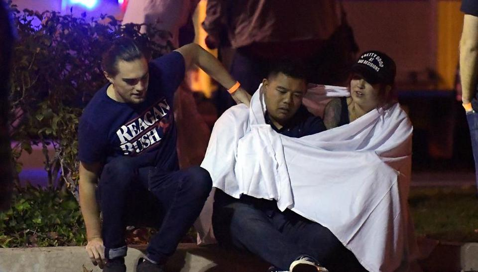 People comfort each other as they sit near the scene on November 8 in Thousand Oaks, California.