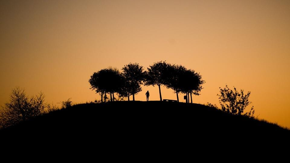 A man takes a stroll as the sun rises behind the Kronsberg hill in Hanover, northern Germany. (Julian Stratenschulte / dpa / AFP)