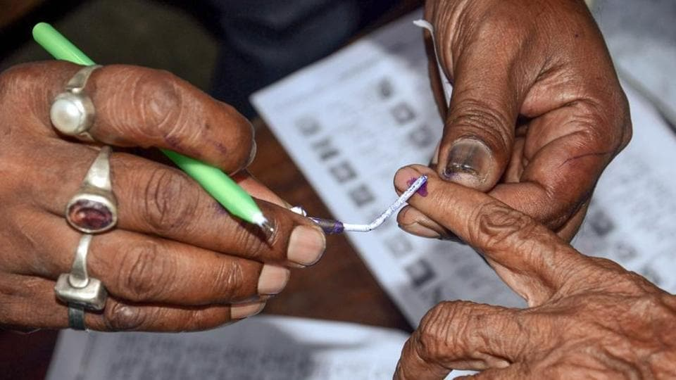 Polling officials put an ink mark on a voter's finger after during panchayat election at a polling booth in Howrah district of West Bengal.