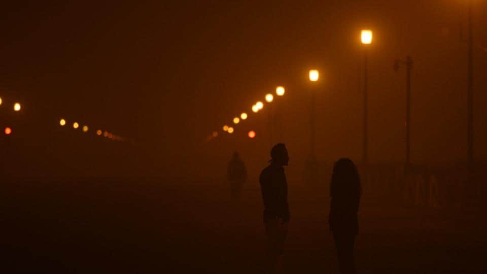 People seen standing on roadside amid heavy smog the day after Diwali, near India Gate, in New Delhi, on Thursday, November 8, 2018.