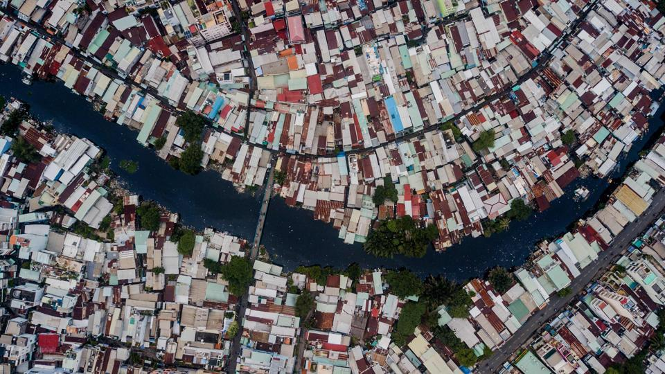 On the banks of Ho Chi Minh City's Xuyen Tam canal the houses come in many forms. Short or tall, pieced together from scraps of wood, or metal or plastic. Some tilt precariously over the polluted water's edge. (Kao Nguyen / AFP)