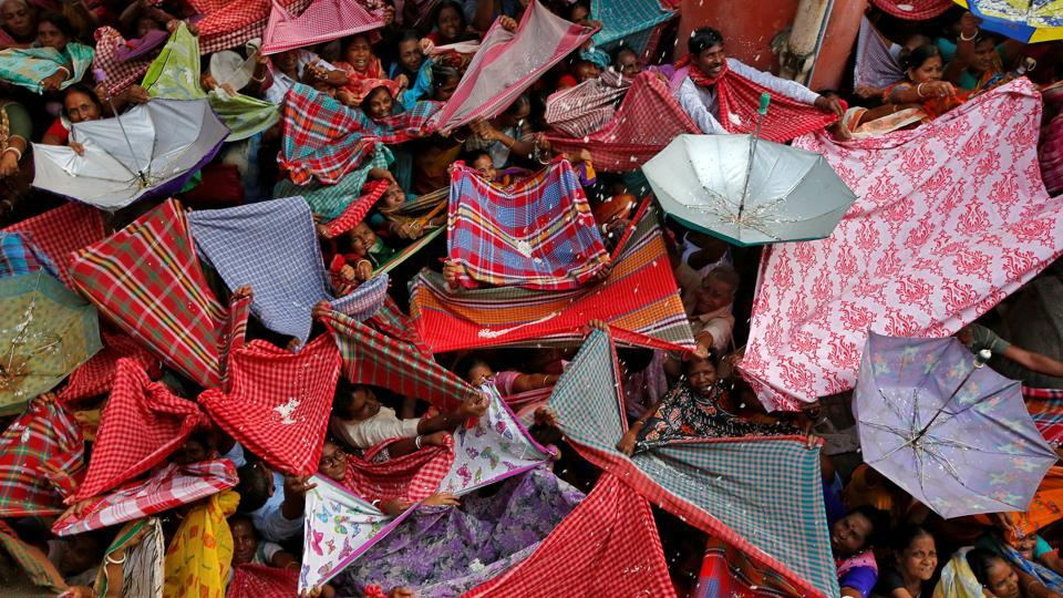 Hindu devotees hold up clothes and umbrellas to receive rice as offerings being distributed by a temple authority on the occasion of the Annakut festival in Kolkata, West Bengal. (Rupak De Chowdhuri / REUTERS)