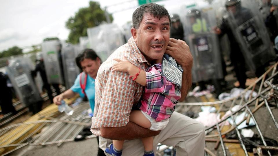 A Honduran migrant protects his child after fellow migrants stormed a border checkpoint in Guatemala, Mexico. Marcelino explained that it was a march that turned into a protest and started to get increasingly chaotic. Being father of nine-year-old girl the situation affected him and after taking the photo, he took others of families coming out of the restrictive cordon created by police. The confusion was brought under control after gas was used to disperse the migrants. (Ueslei Marcelino / REUTERS)
