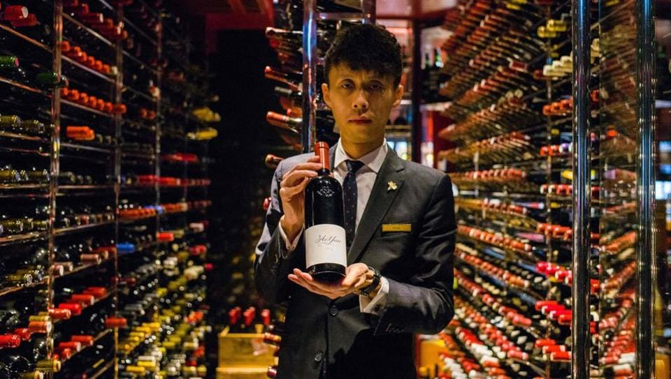 Assistant sommelier Felix Ho Ho Yua poses with a 2014 bottle of Ao Yun red wine at the Robuchon restaurant wine cellar in Hong Kong. A $300 bottle of wine sold in the United States and Europe is made in the unlikeliest of places, at the foot of the Himalayas in China. A stone's throw away from Tibet, Ao Yun's vineyards are located beneath the sacred Meili Mountain at altitudes ranging up from 2,200 metres in Yunnan. (Anthony Wallace / AFP)