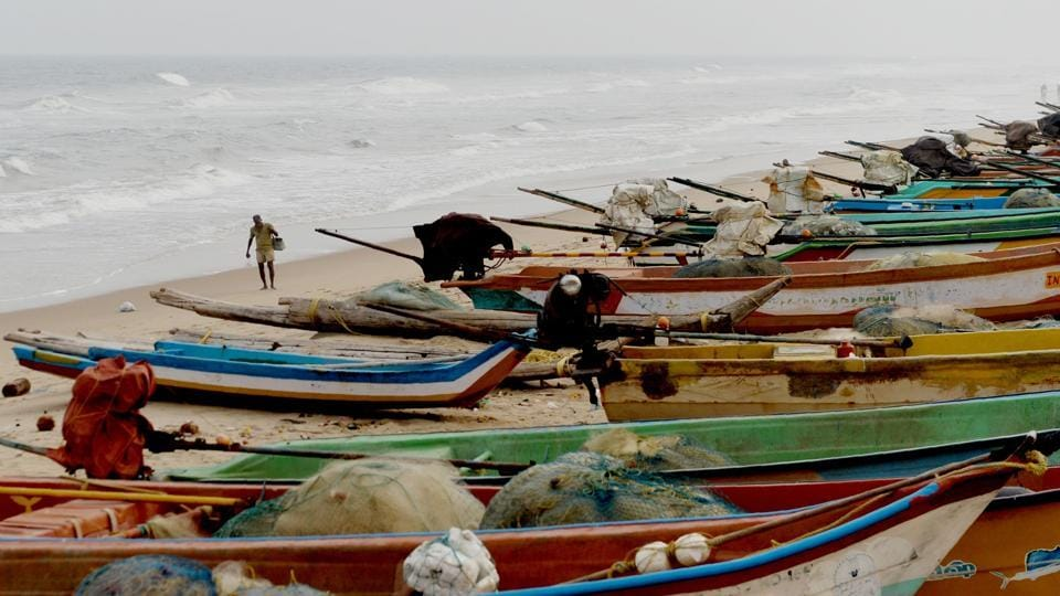 An Indian fisherman walks along a beach beside fishing boats on the coast of the Bay of Bengal in Chennai.