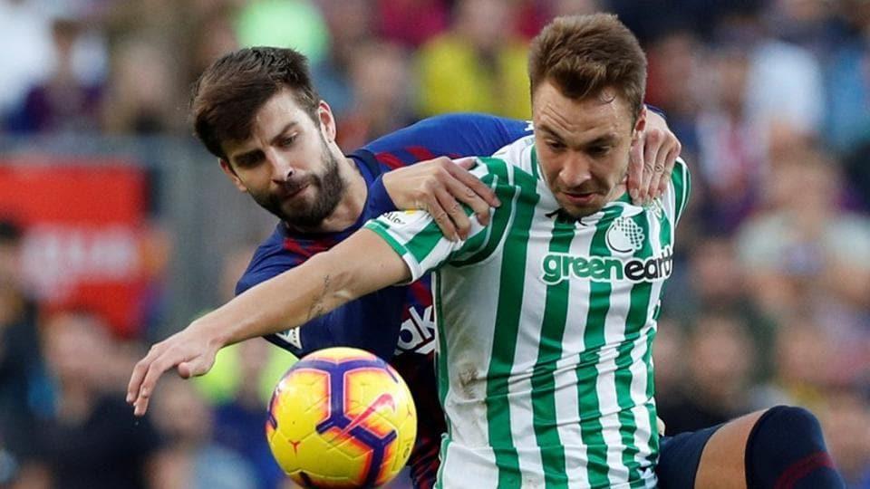 Real Betis' Loren Moron in action with Barcelona's Gerard Pique.