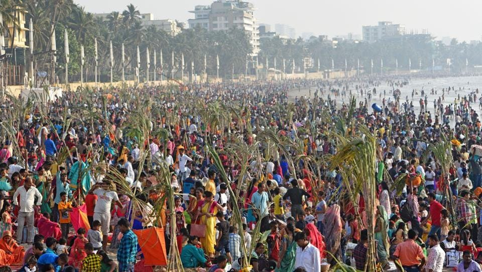 Devotees offer prayers to the sun god after taking bath at Juhu Chowpatty in Mumbai. Huge crowds of fasting worshippers accompanied by their family members, relatives and friends thronged to the ghats in all parts of the country. (Satyabrata Tripathy / HT Photo)