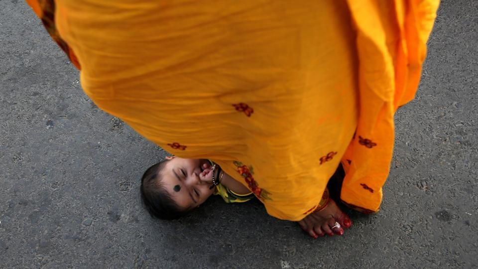 A woman steps over an infant in a ritual seeking blessings for the infant from the sun god during the festival in Kolkata. The challenging fasting is observed by lady folks or married women for the well-being of their sons and the happiness of family members. (Rupak De Chowdhuri / REUTERS)