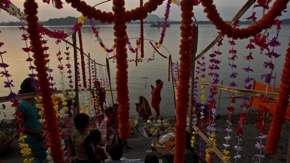 A group of devotees perform rituals in the Brahmaputra river, Guwahati. On the last day, which is the also is known as 'doosra argha', devotees offer their prayers to the sun god on the river banks before the sunrise and conclude their fast and eat special prasad and delicacies made for the festival. (Anupam Nath / AP)