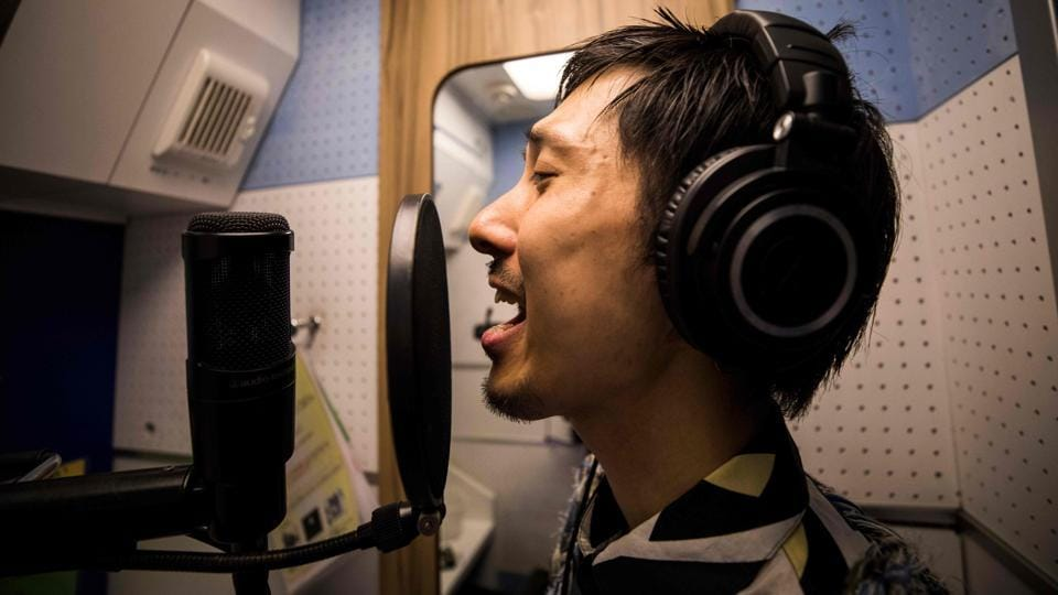 """Every so often, 33-year-old Masaki Kitakoga slips into a tiny booth with a desk and a chair and belts out karaoke tunes for 90 minutes -- completely on his own. Kitakoga is part of a growing trend in Japan favouring solo activities that is now so widespread it has its own name: """"ohitorisama"""" or """"on your own."""" (Behrouz Mehri / AFP)"""