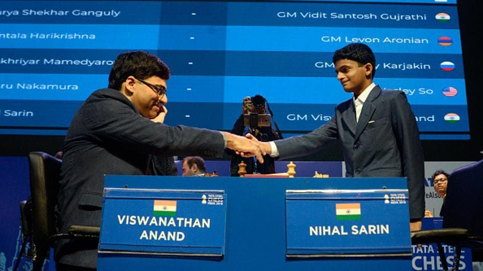 Indian chess Grandmaster Viswanathan Anand (left) greets Indian chess Grandmaster Nihal Sarin (right) before the eightieth round matches of rapid chess at Tata Steel Chess India 2018