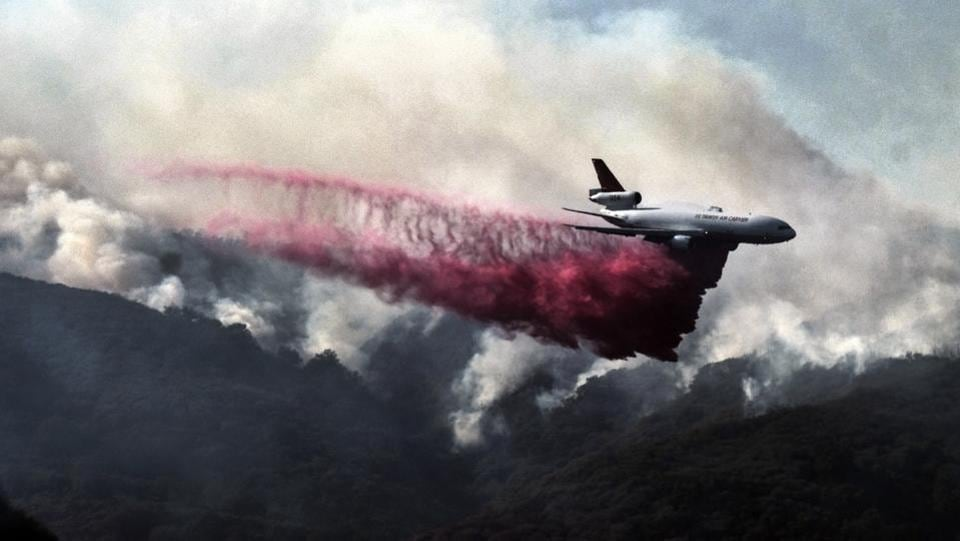 A firefighting DC-10 makes a fire retardant drop over a wildfire in the mountains near Malibu Canyon Road in Malibu, California on November 11, 2018. (Richard Vogel / AP)