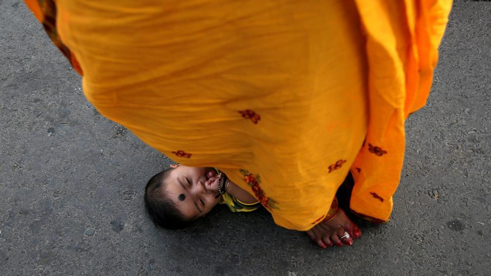 A Hindu woman steps over an infant in a ritual seeking blessings for the infant from the sun god during the religious festival of Chhath Puja in Kolkata, west Bengal. (Rupak De Chowdhuri / REUTERS)