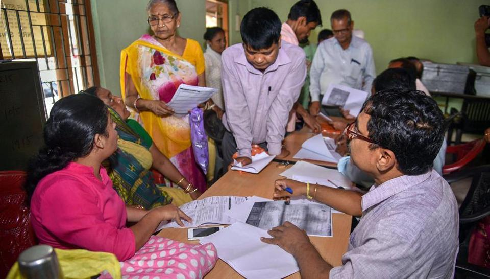 People verify the National Register of Citizens (NRC) forms to file claims and objections at an NRC centre in Guwahati.