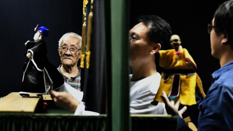"Chen stands next to a puppet show being performed by his students. Puppet master vows to continue performing and teaching as long as he still has the strength. ""I haven't completed passing on the art so I can't retire,"" he said. (Sam Yeh / AFP)"