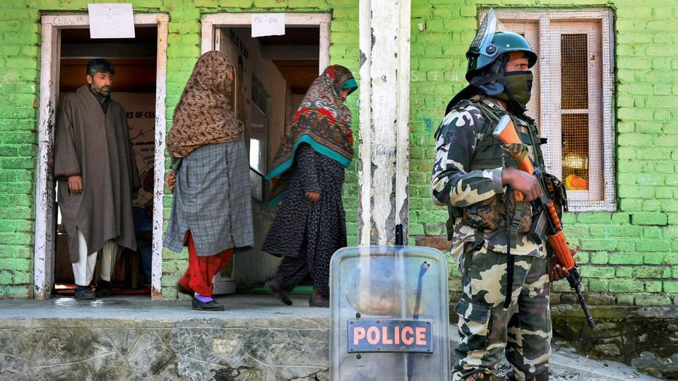 Voters leave after casting their vote as a security personnel stands guard at a polling station during the second phase of Panchayat elections at Kangan, Jammu and Kashmir's Gandrebal district on Tuesday. (PTI)