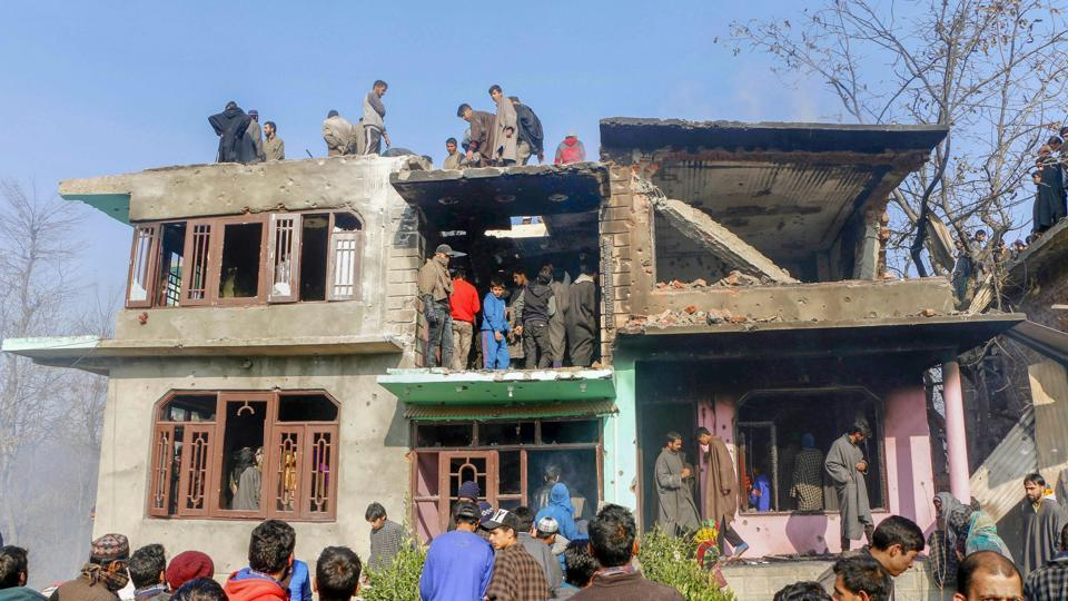 People inspect a damaged house where four Hizbul Mujahideen militants and a soldier were killed during an encounter, at Shopian district of South Kashmir on November 20.