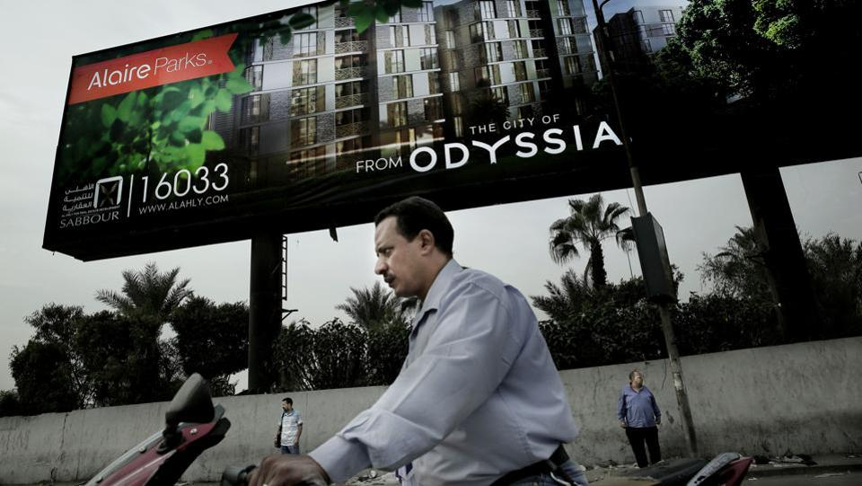"""A man rides his motorbike as others wait for a bus under a billboard promoting new residential housing, in Cairo, Egypt. Billboards across Cairo advertise luxury homes with """"breathtaking"""" views and names like """"La Verde"""" or """"Vinci"""" in Egypt's new capital that is under construction in the desert, miles from the Nile-side city which has been the seat of power for more than 1,000 years. (Nariman El-Mofty / AP)"""