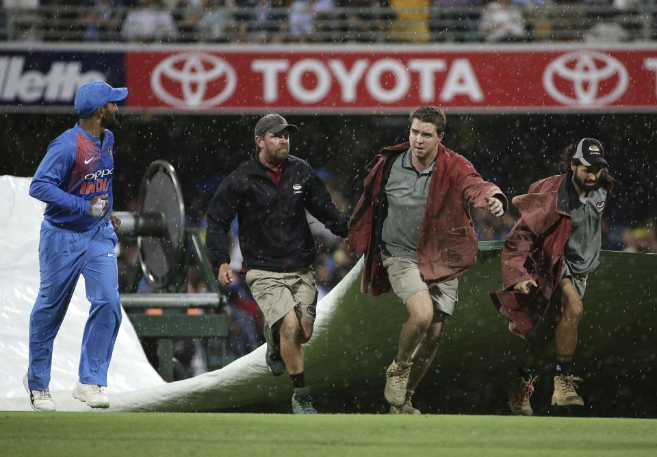 Players leave the field as ground staff cover the pitch after rain stopped play during the first T20 International cricket match between Australia and India in Brisbane. (AP)