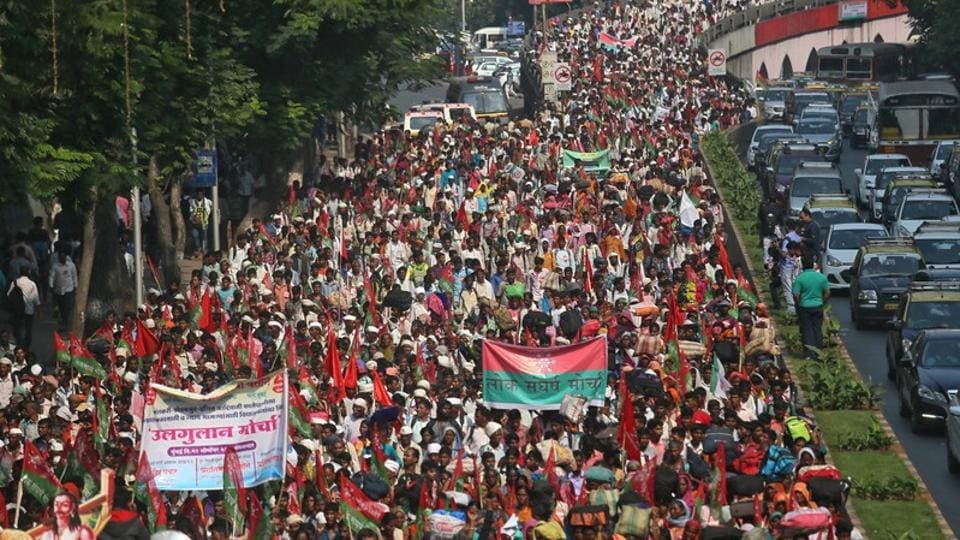 Farmers march on a flyover during a protest rally demanding loan waivers and the transfer of forest lands to villagers who have farmed there for decades, in Mumbai.