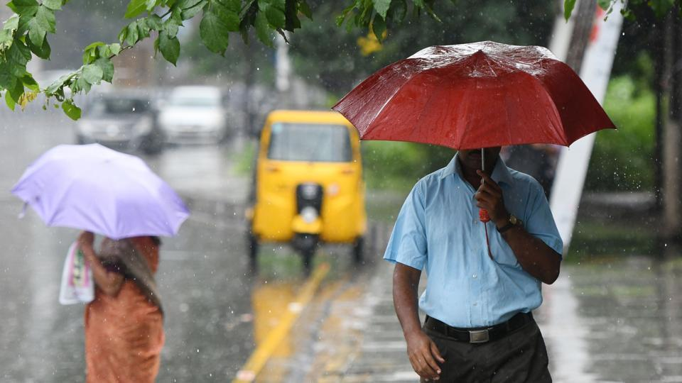 Pedestrians walk with umbrellas during heavy rain in Chennai on November 21, 2018.