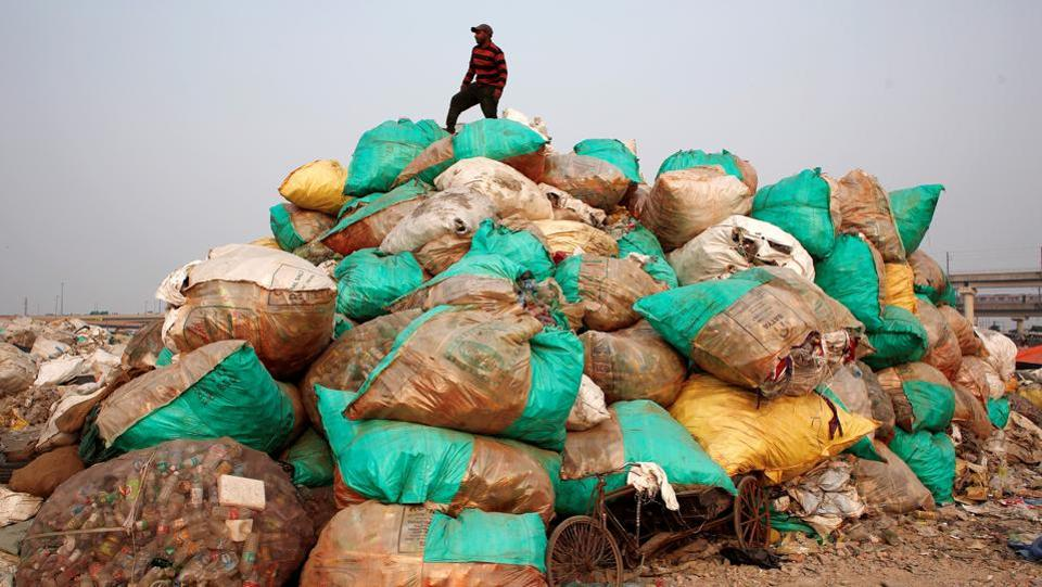 A man stands on a pile of sacks containing discarded plastic bottles at a recycling yard in New Delhi on November 22, 2018. (Adnan Abidi / REUTERS)