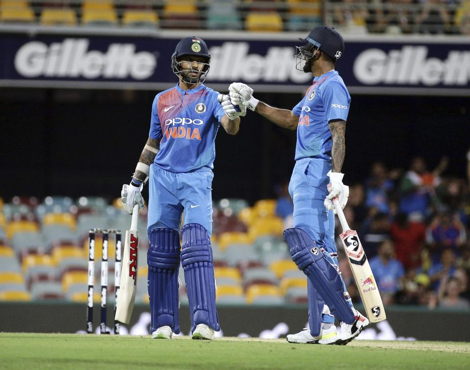 India's Shikhar Dhawan, left, and K.L. Rahul, right, greet after Dhawan reached 50 runs during the first T20 International cricket match between Australia and India in Brisbane. (AP)