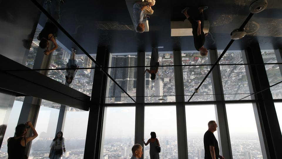 Tourists are reflected in ceiling mirrors as they view the Bangkok cityscape during a visit of the King Power Mahanakhon building Bangkok, Thailand. (Sakchai Lalit / AP)