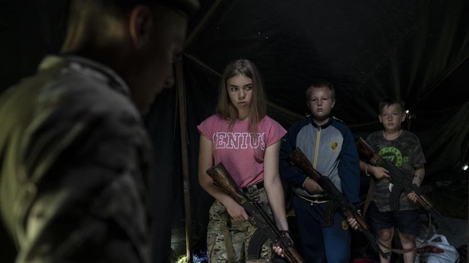 Stumbling out of their tents, soldiers in training struggled to hold AK-47s that were, in some cases, almost as tall as they were. They were required to carry the heavy rifles all day, and one of the girls broke down in tears from exhaustion. (Felipe Dana / AP)