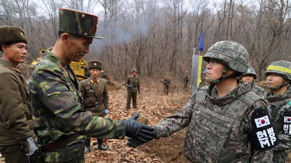 A South Korean military officer (R) and a North Korean military officer shake hands during an operation to reconnect a road across the Military Demarcation Line inside the Demilitarised Zone (DMZ) separating the two Koreas. (Yonhap / The Defense Ministry / REUTERS)