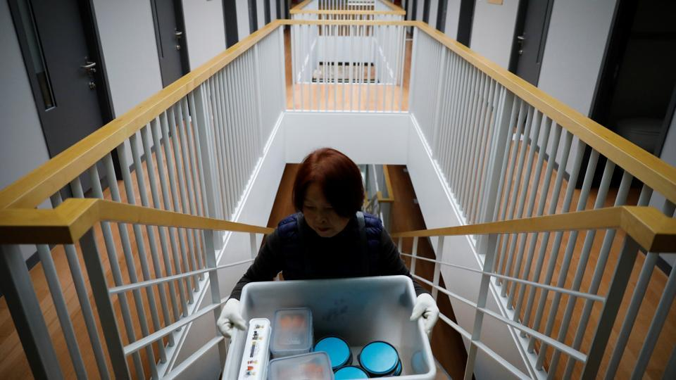 An administrator serves meals. The menu includes steamed sweet potato and a banana shake for dinner, and rice porridge for breakfast. Co-founder Noh Ji-Hyang said the mock prison was inspired by her husband, a prosecutor who often put in 100-hour work weeks. (Kim Hong-Ji / REUTERS)