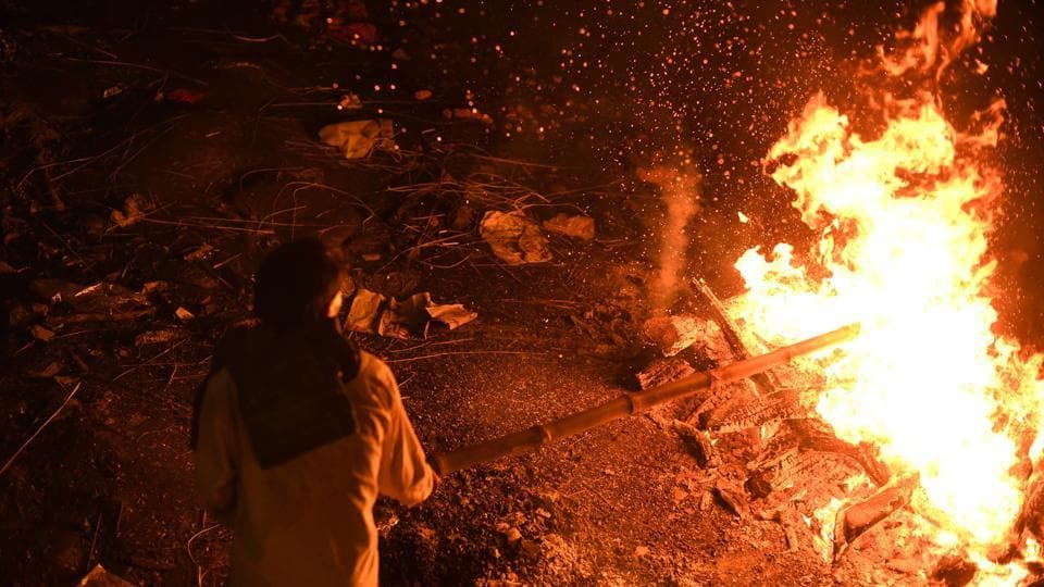 A man stokes a funeral pyre at the traditional crematorium grounds at Harischandra Ghat on the river Ganga in Varanasi, Uttar Pradesh. The ghats of this ancient city witness around 200 cremations per day on the banks of the country's holiest river. (Dominique Faget / AFP)