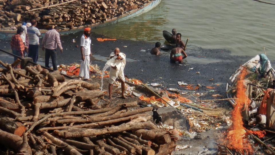 Men search for valuable metals such as gold and silver from dead bodies at Manikarnika Ghat. As the bodies wrapped in white shrouds and marigold flowers turn to ash, the remains are collected and sprinkled in the river. At the ghats, the Doms pass flaming torches to the families of the deceased, who ignite the wooden pyres dotting the riverside. (Dominique Faget / AFP)