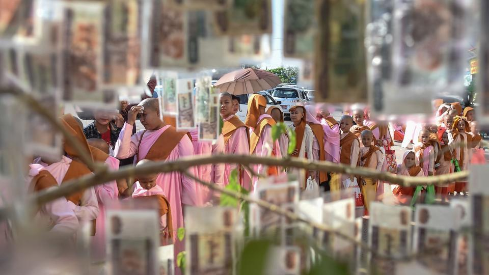 Novice monks walking during alms procession are seen through a hanging donations of Myanmar currency notes during Buddhist religious festivities in Yangon. (Ye Aung Thu / AFP)