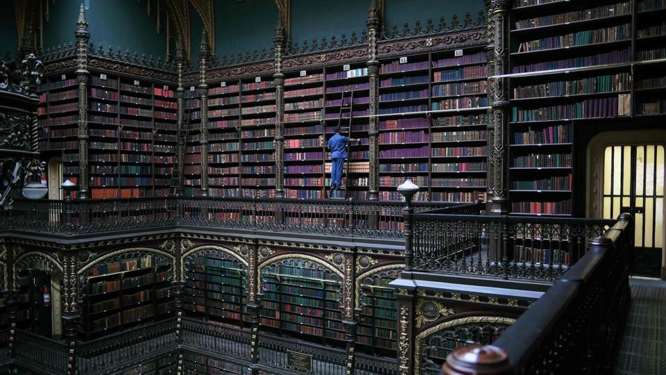 Employee Jeferson Deodata da Silva selects a book from the shelves of the Royal Portuguese Cabinet of Reading in Rio de Janeiro, Brazil. (Carl De Souza / AFP)