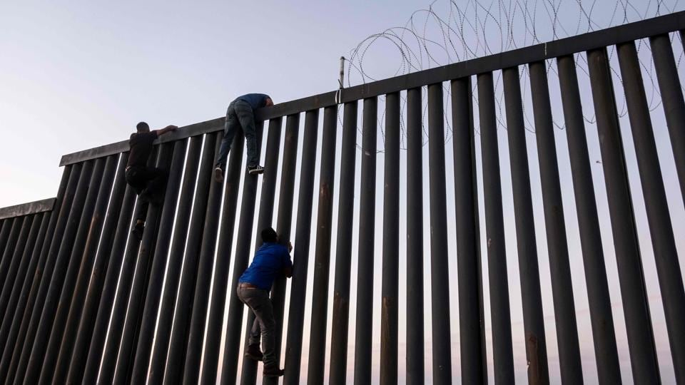 Men from Mexico climb the US-Mexico border wall in Playas de Tijuana, northwestern Mexico. (Guillermo Arias / AFP)