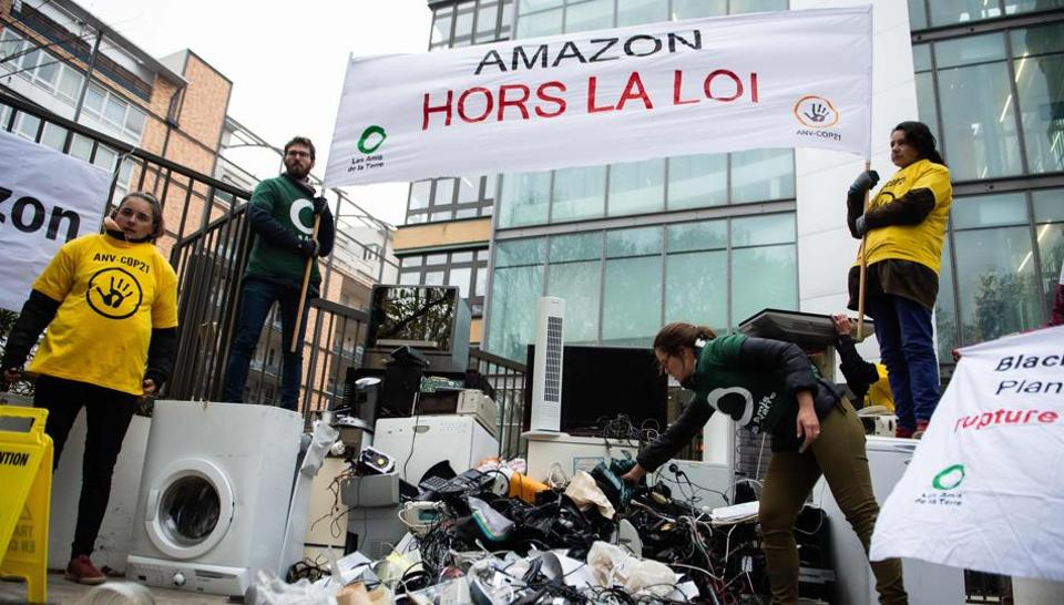 Activists of French NGOs 'Les Amis de la Terre' (Friends of the Earth) and ANV Cop21 dump trashed appliances in front of the French headquarters of US online retailer Amazon on November 23, 2018 in Clichy, northwest of Paris, during a protest against the company and on the first day of the Black Friday sales.