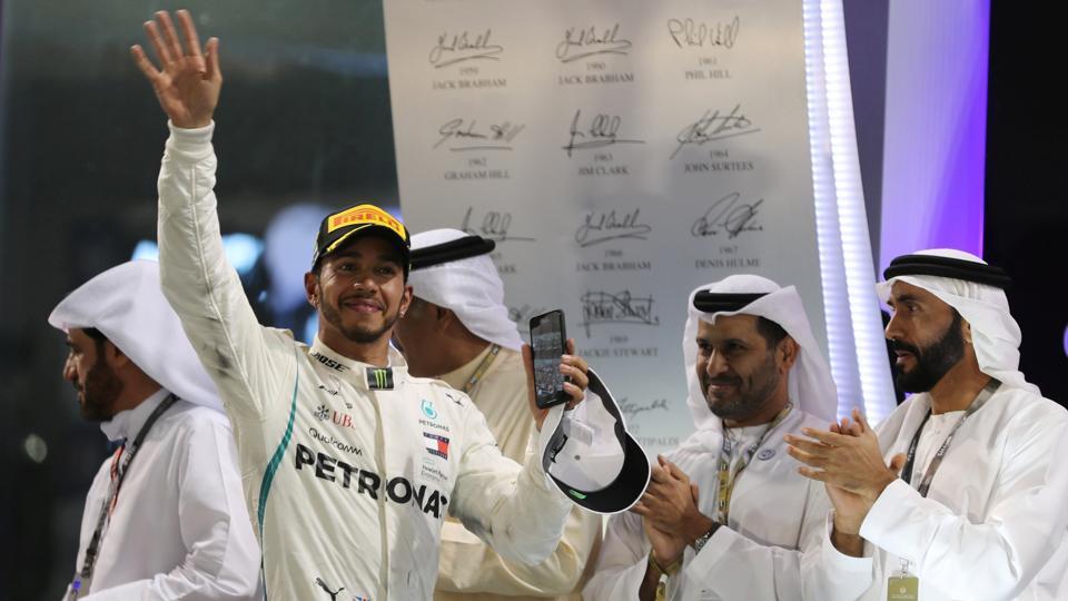Mercedes' Lewis Hamilton celebrates winning the race on the podium.