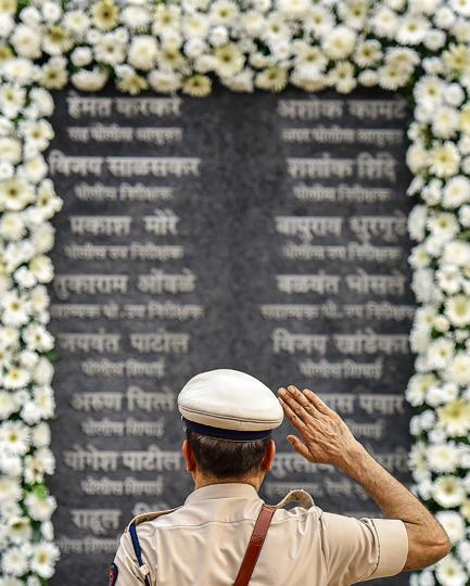 A police officer pays his respects at Martyrs' Memorial to those who laid down their lives defending the city against the terror attacks.