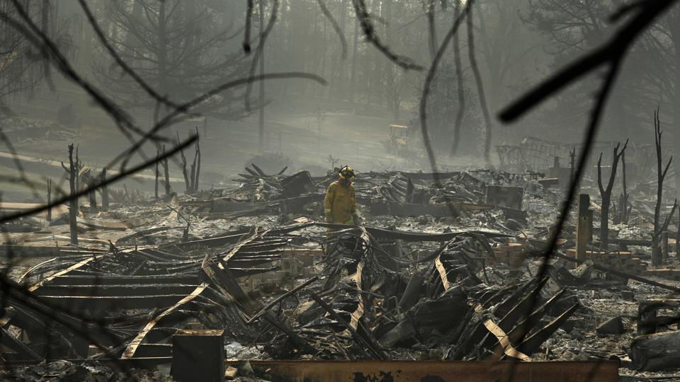 A firefighter searches for human remains in a trailer park destroyed in the Camp Fire, in Paradise, California. The massive wildfire that killed dozens of people and destroyed thousands of homes has been fully contained after burning for more than two weeks.