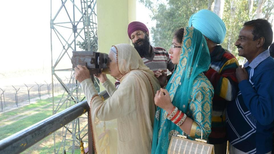 An Indian Sikh devotee looks through binocular towards the Gurdwara Kartarpur Sahib, which is situated in Pakistan, from Indian side at Dera Baba Nanak on the outskirts of Amritsar on November 25, 2018