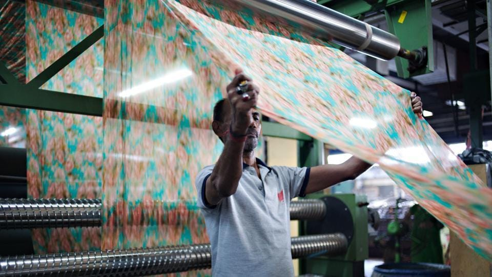 A worker inspects a piece of printed fabric as it runs through a machine during the manufacturing of Lakshmipati Sarees brand garments at the Siddhi Vinayak Knots & Prints Ltd. factory in Surat, Gujarat. The manufacturing sector contributes about 15 percent of the India's gross domestic product.