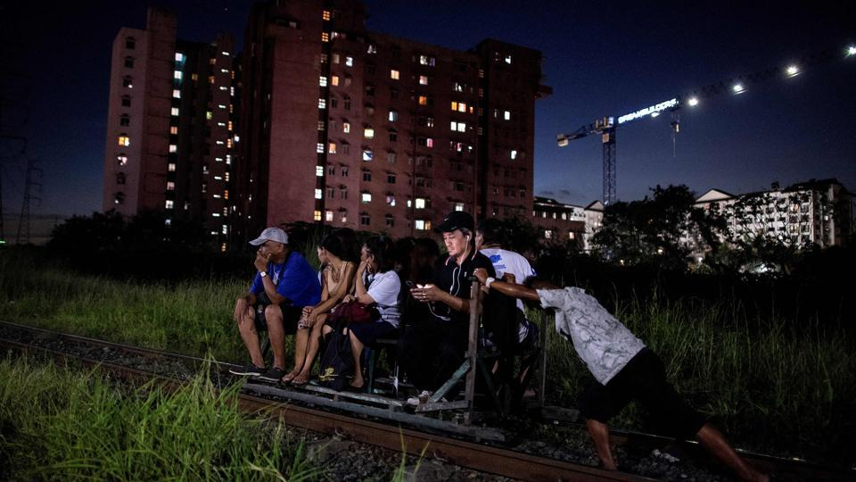 """As soon as the train rumbles past, the men heave their home-made pushcarts back onto the tracks and passengers hop aboard -- cheating death and beating Manila's notorious traffic. Scores of commuters in the city of about 12 million are propelled to their destinations daily by so-called """"trolley boys"""" pushing metal carts that ply a few segments of the sprawling capital's railroads. (Noel Celis / AFP)"""
