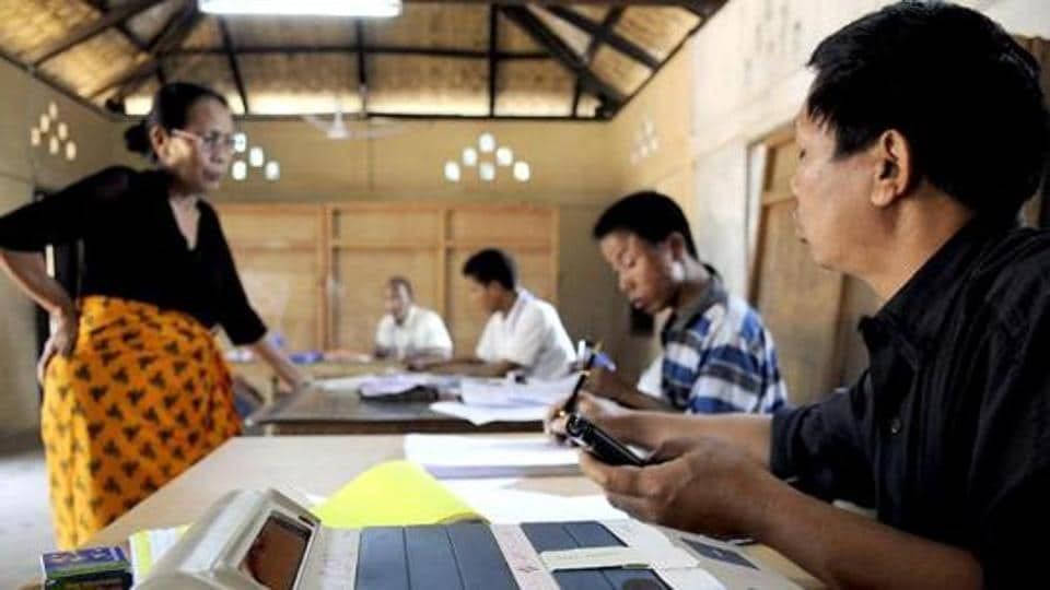 Election Commission official administers voting papers at a polling station at Bungthuam, on the outskirts of Aizwal, in Mizoram.
