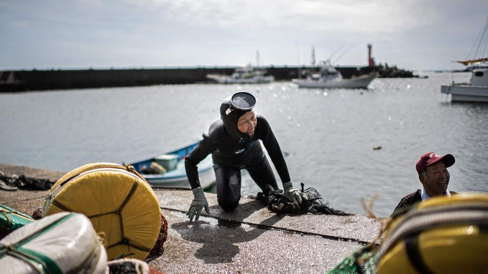 A freediving fisherwoman, known as an 'ama', climbs ashore after a dive in Toba. A group of Japanese grannies follows from a boat returning to shore. Clad in black wetsuits and bubbling with energy, they are part of a dwindling community of ama -- freediving fisherwomen. (Martin Bureau / AFP)